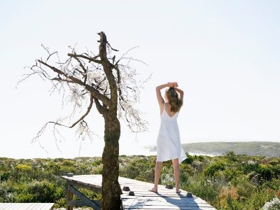 woman in white dress standing outside on a dock with her arms in the air