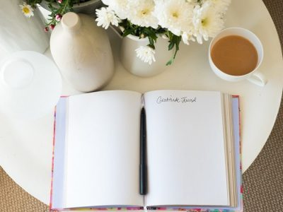 blank gratitude journal with pen on desk with tea and flowers