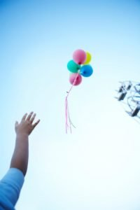boy letting balloons go into the sky