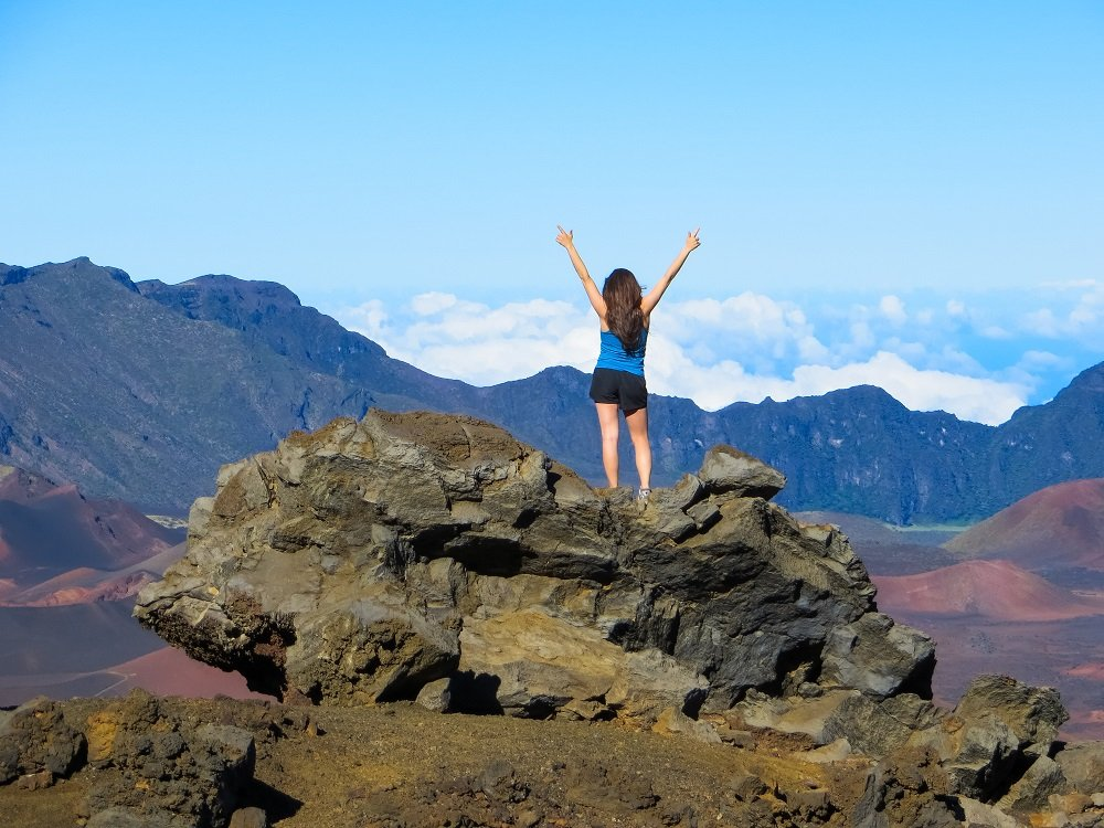 Monica Nedeff raising her arms standing on top of a boulder in Haleakala National Park