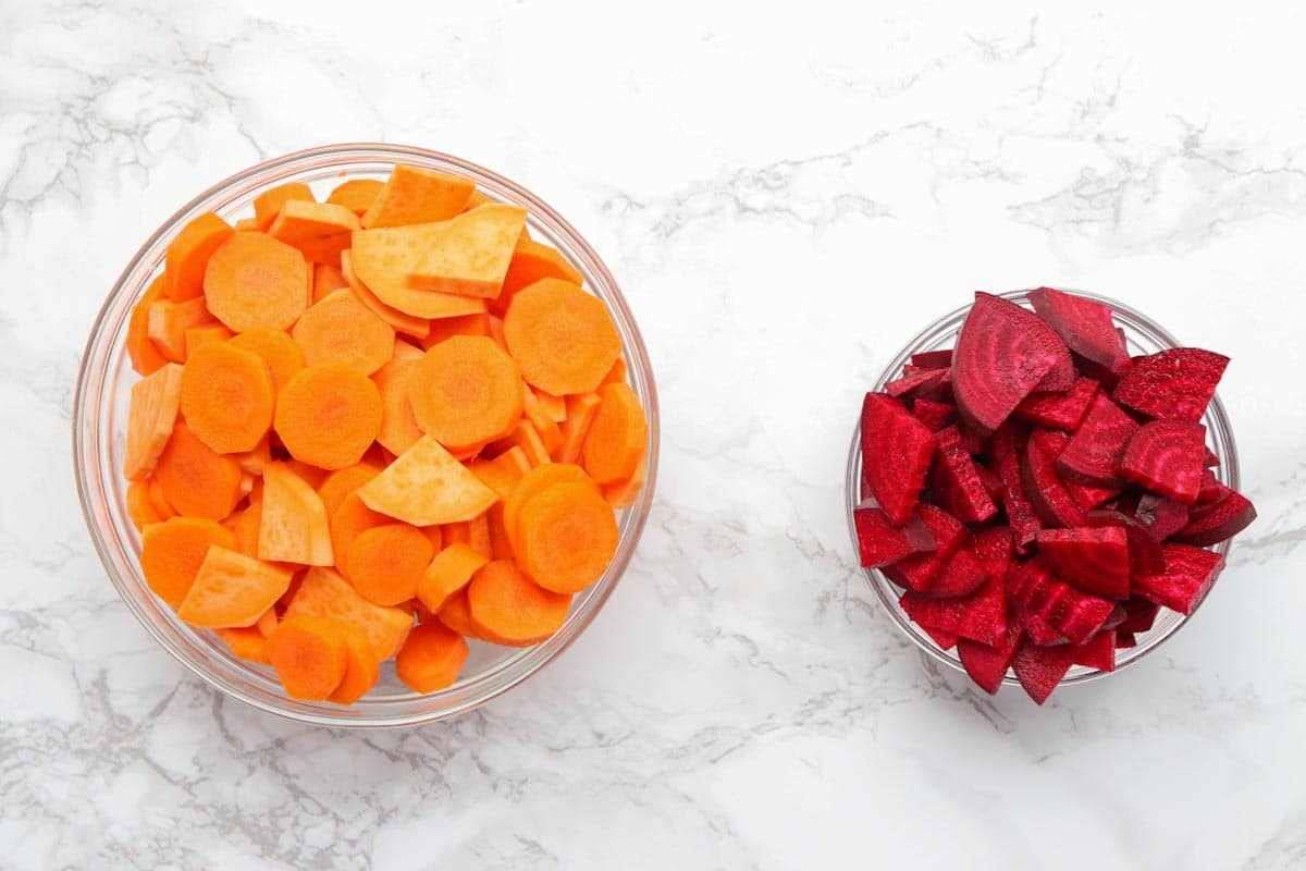 chopped carrots and sweet potatoes in a bowl and chopped beets in a separate bowl