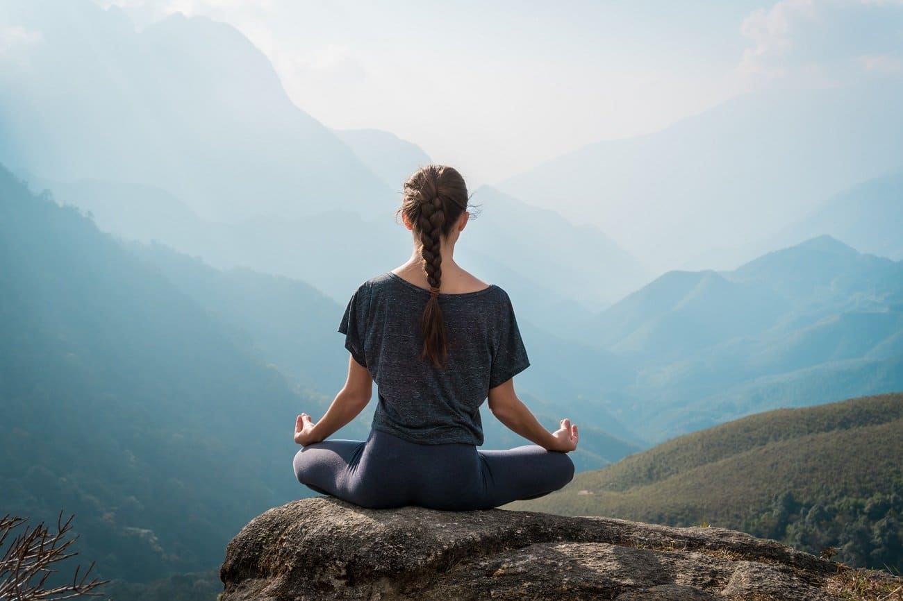 Woman meditates seated on top of a mountain