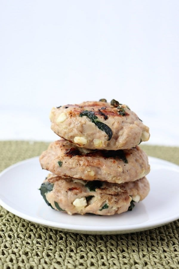 three grilled turkey burgers with chunks of feta and spinach stacked on a plate