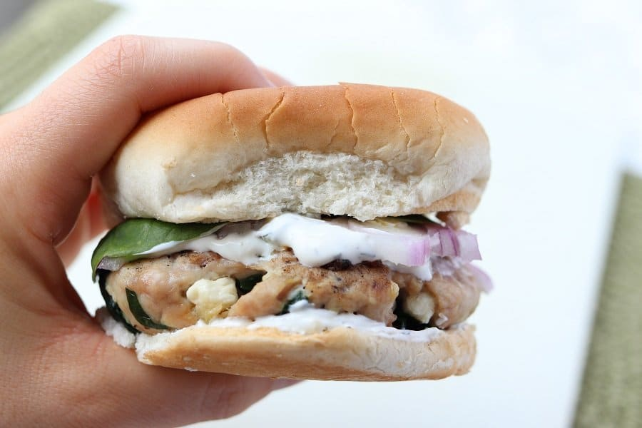 Hand holding a turkey burger with tzatziki dripping down the bun