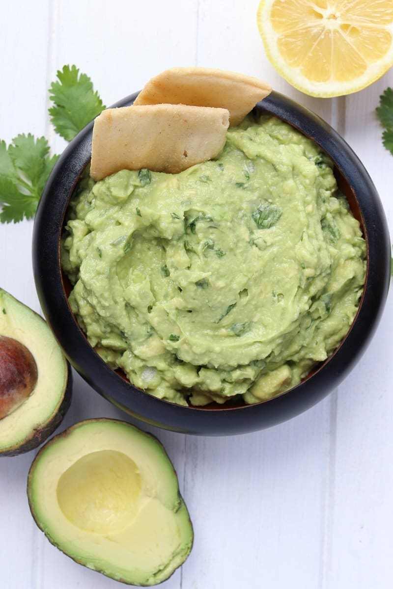 guacamole in a bowl garnished with cilantro and a lemon wedge