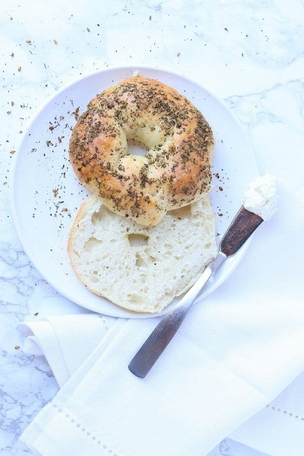 zaatar bagel sliced on a plate next to a knife with cream cheese
