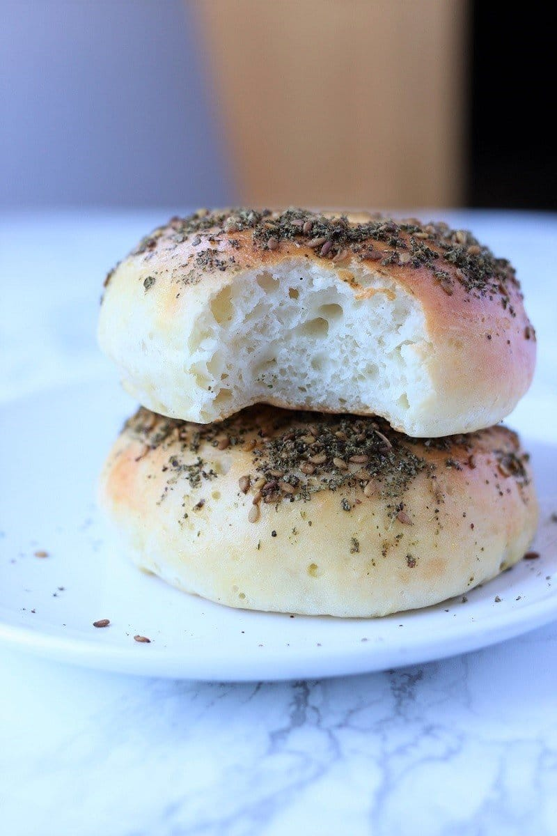 two zaatar bagels stacked on a plate with a bite taken out of the top bagel