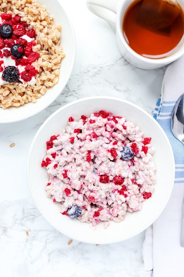 Yogurt and berries mixed with farro served in a white bowl