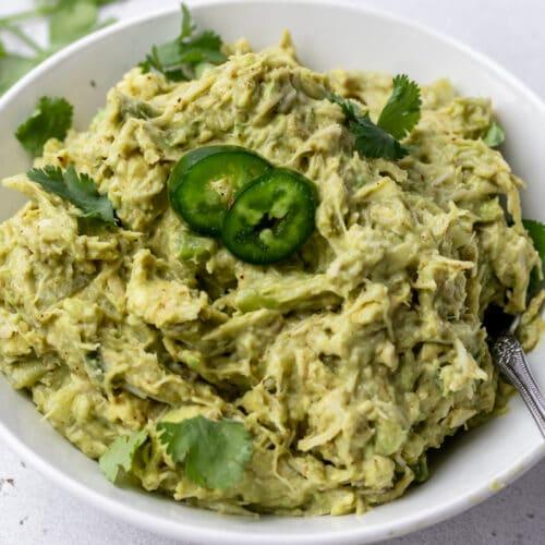 spoon in a bowl of guacamole chicken salad