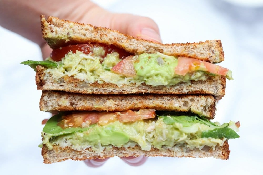 close up of hand holding two guacamole sandwich halves with spinach and tomato