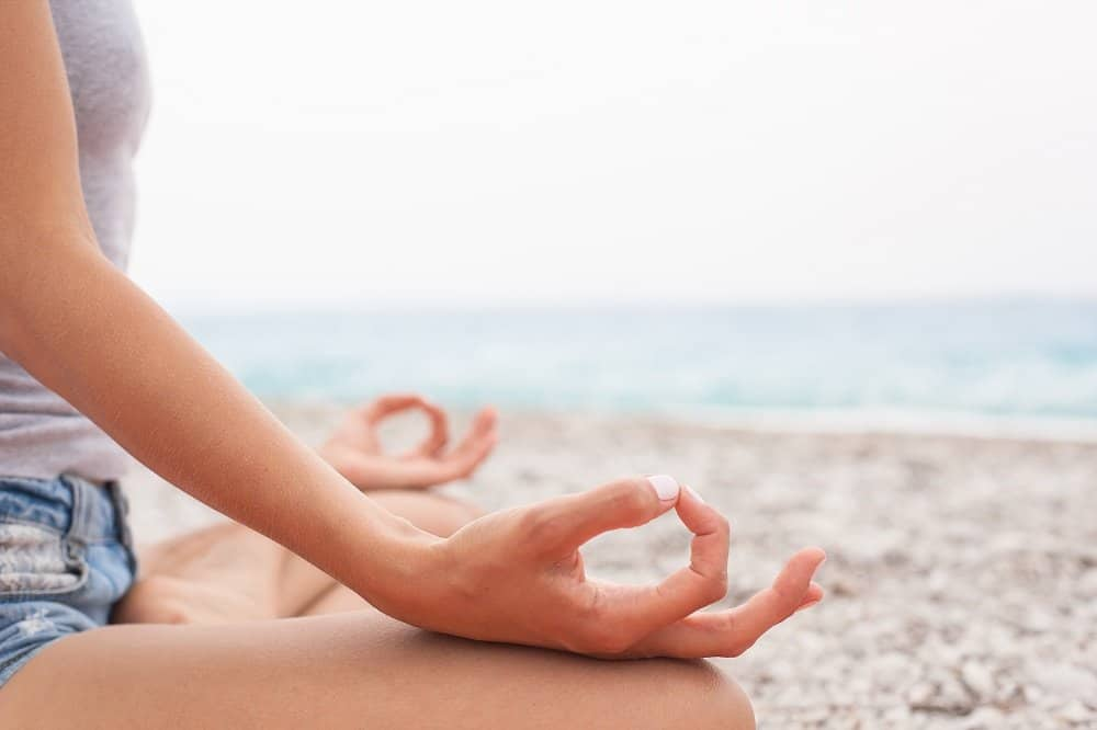 girl meditating on the beach with hands resting on legs