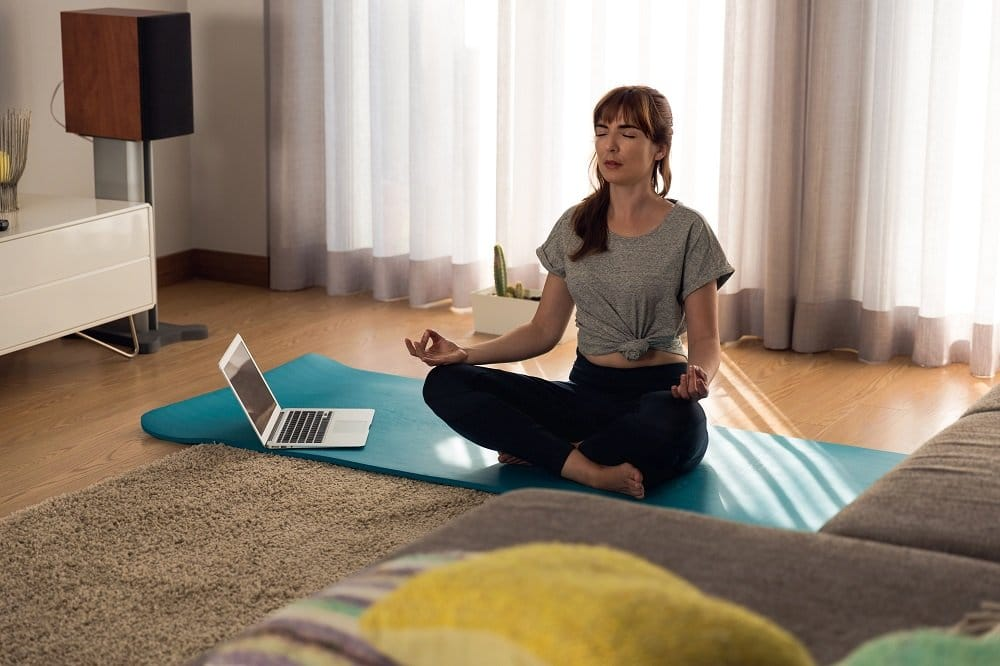 girl meditating sitting cross legged on yoga mat in her living room