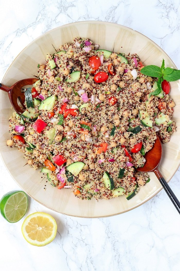large bowl of quinoa, tomatoes, cucumbers and mint leaves