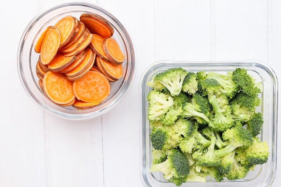two glass containers of sliced raw sweet potatoes and chopped raw broccoli