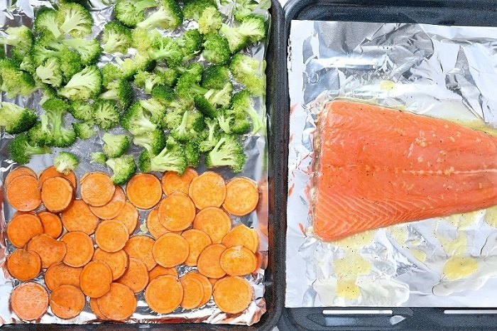 salmon and vegetables on separate foil lined sheet pans ready for broiling