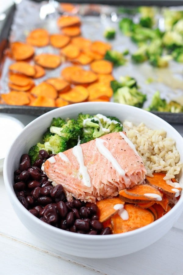 salmon buddha bowl drizzled in maple tahini dressing in front of sheet pan of extra veggies
