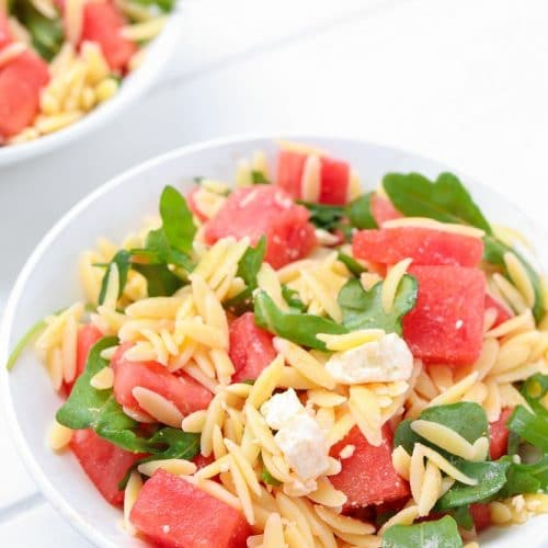 white bowl of orzo mixed with watermelon, feta cheese and arugula