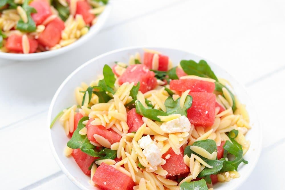 watermelon orzo salad close up with chunks of feta and arugula leaves