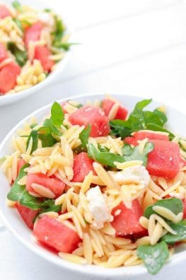 close up of chopped watermelon, orzo and arugula in a salad bowl