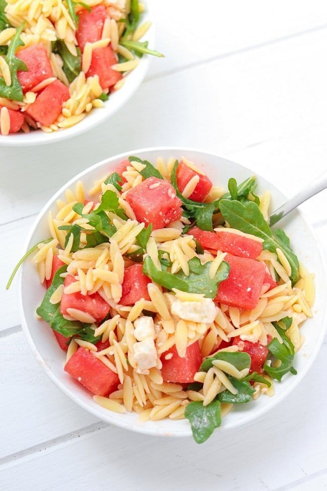 spoon in a bowl of orzo salad with chunks of watermelon