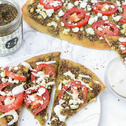 plate of za'atar pizza slices with tahini sauce drizzled on top