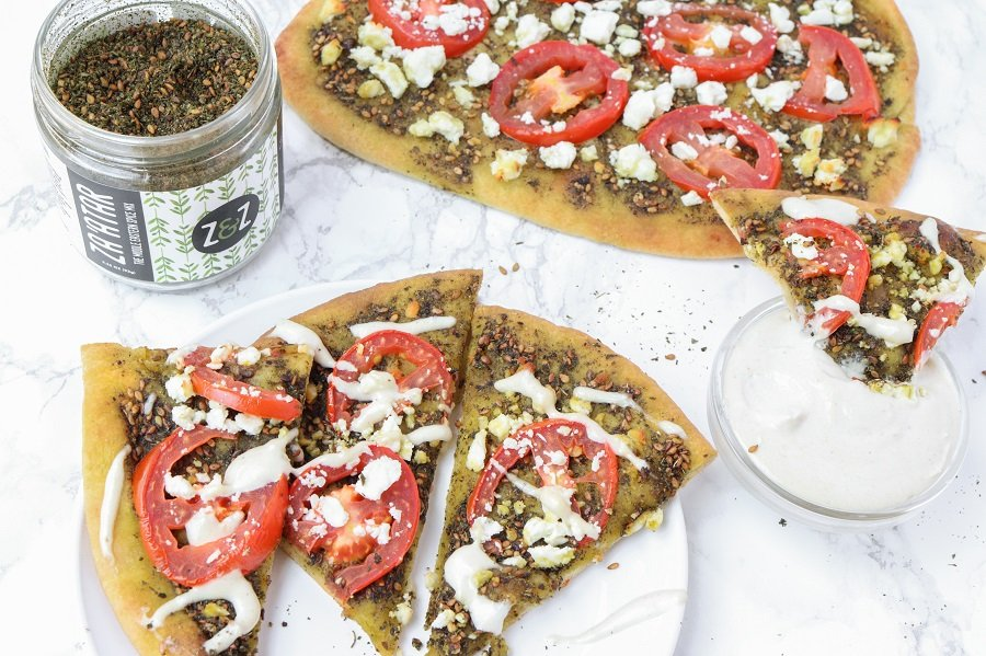 plate of zaatar pizza slices with tahini sauce drizzled on top