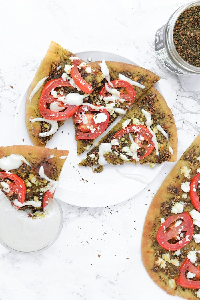 zaatar pizza cut up and dunked in tahini sauce
