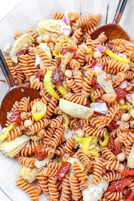 large serving bowl of red lentil pasta salad