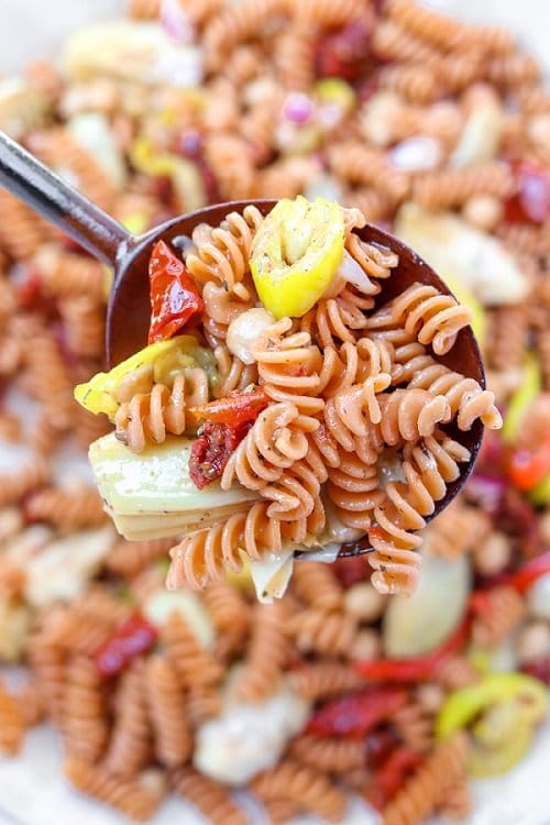 red lentil pasta salad with artichoke, banana peppers and sun-dried tomatoes scooped on a spoon