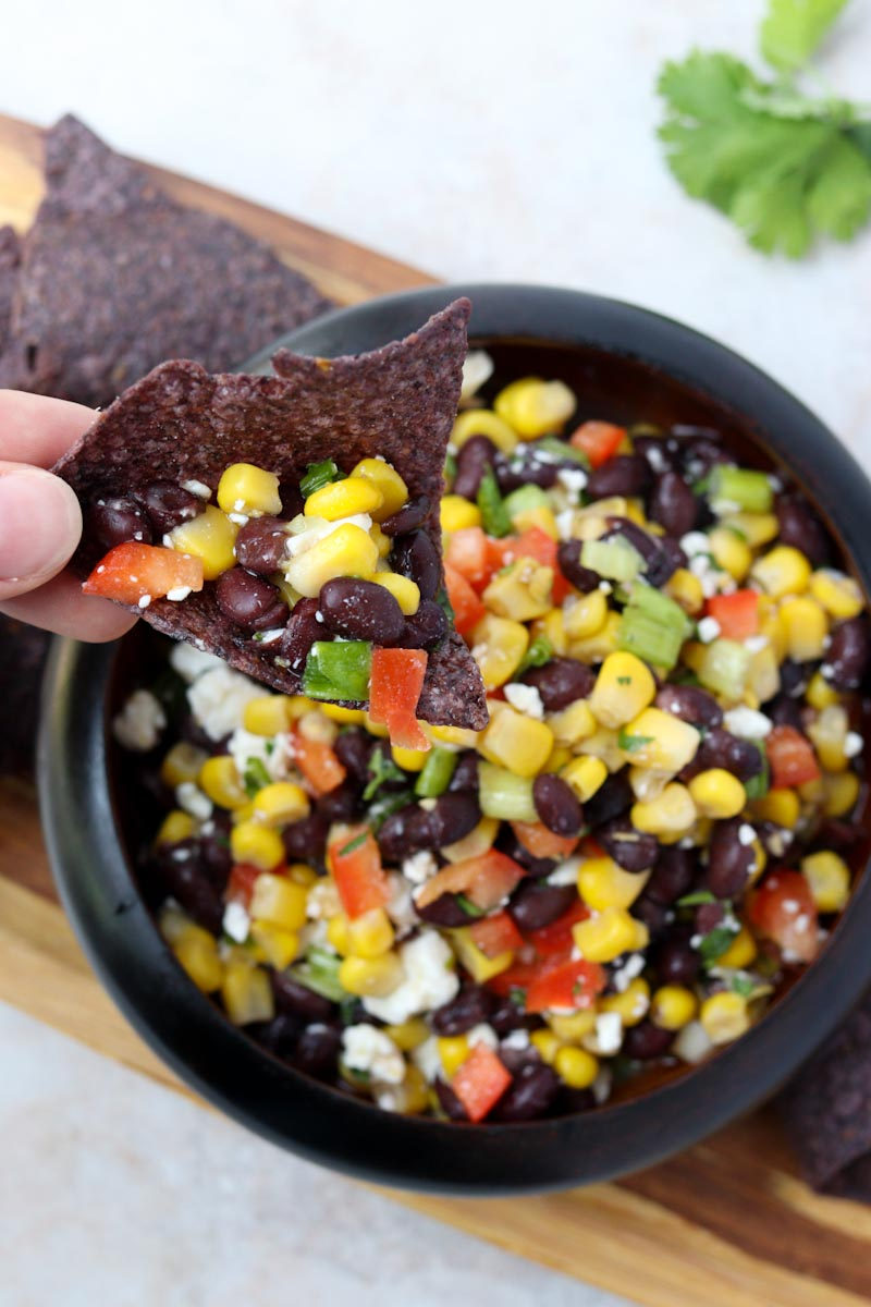 black tortilla chip topped with black bean and corn salsa