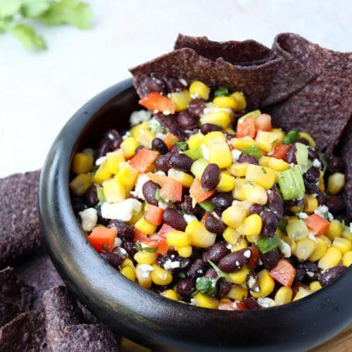 black tortilla chips sitting in a bowl of black bean and corn salad