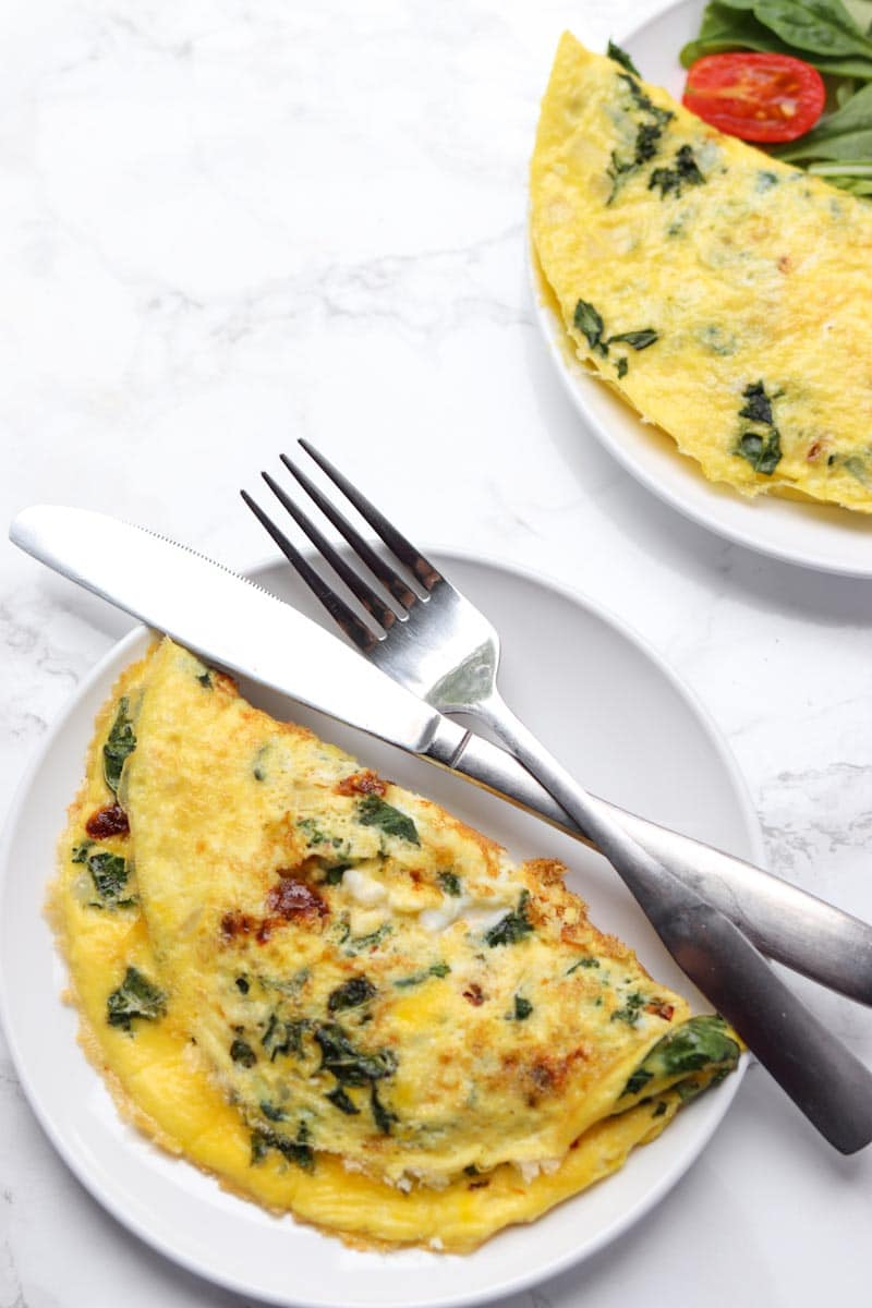 two omelettes on separate white plates with a fork and knife resting one plate