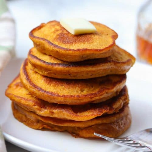 five pumpkin pancakes staked on a plate with a pad of butter on top