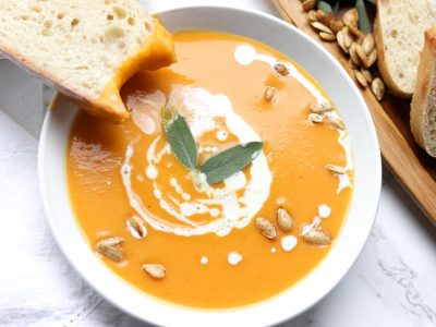 butternut squash soup topped with coconut cream, seeds and sage leaves