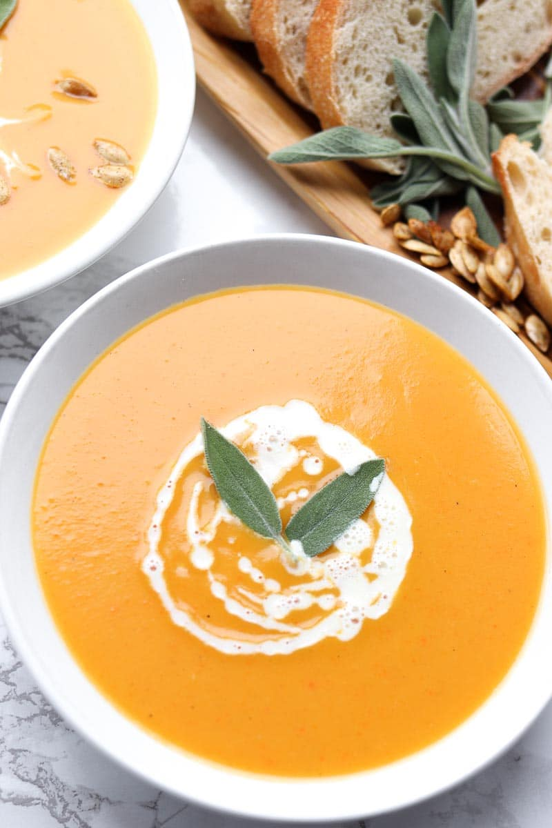 bowl of soup made of butternut squash, carrots and ginger with coconut cream swirled on top
