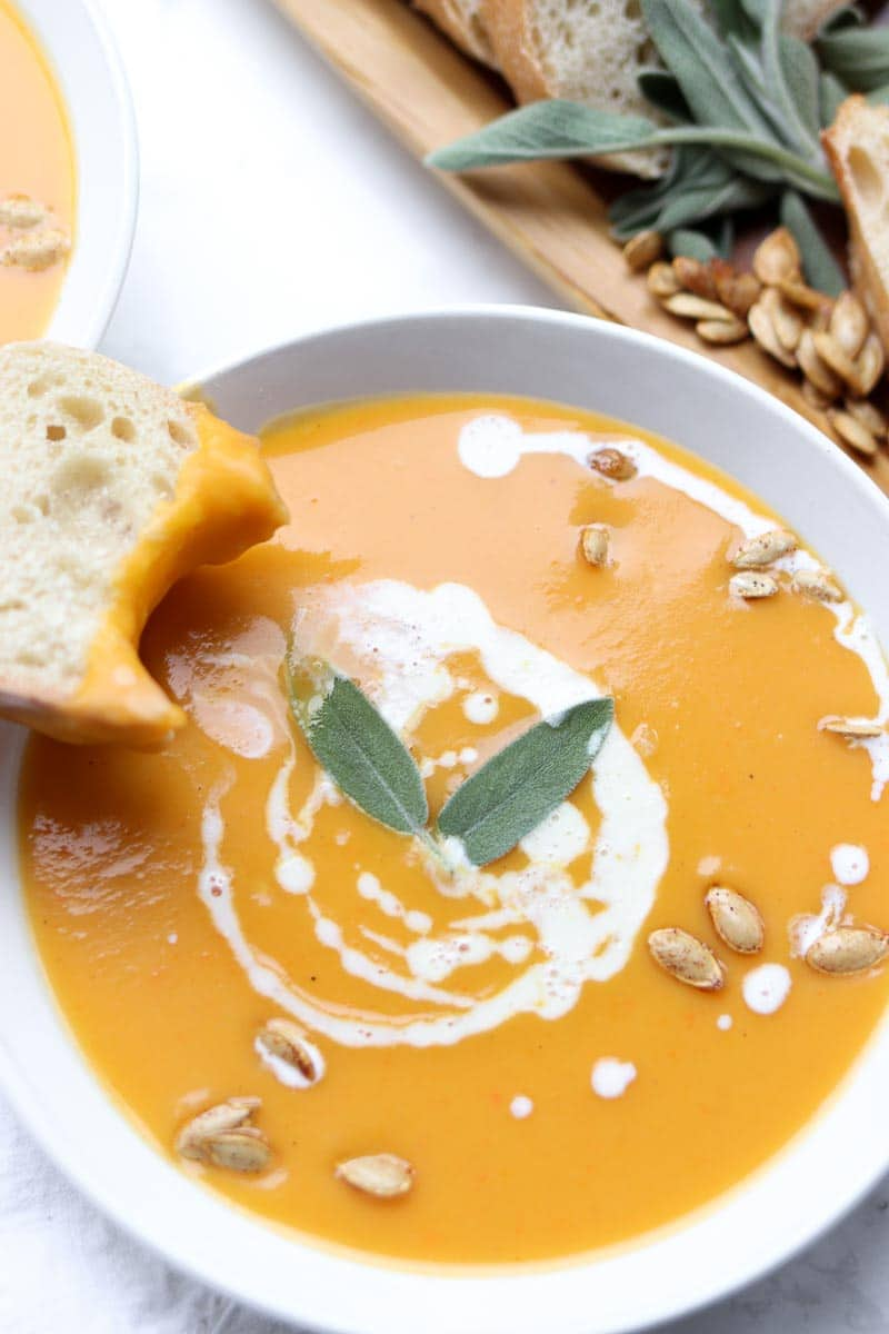 bread sitting on a bowl of butternut squash soup