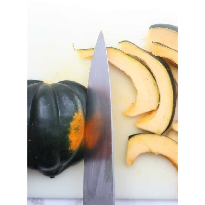 Knife slicing acorn squash into slices on a cutting board