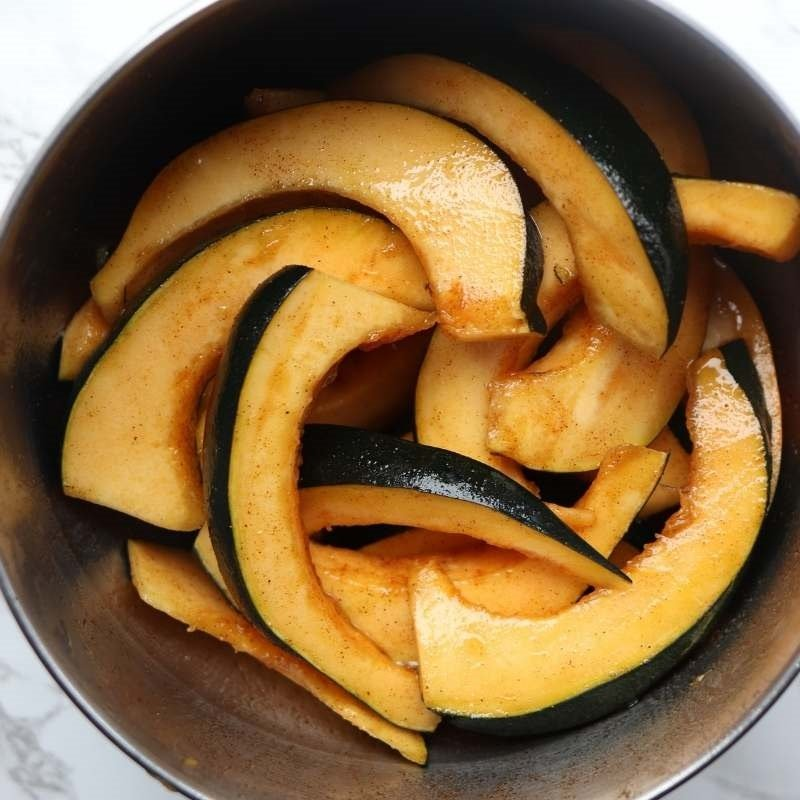 acorn squash slices covered in maple syrup, cinnamon, cayenne pepper and paprika