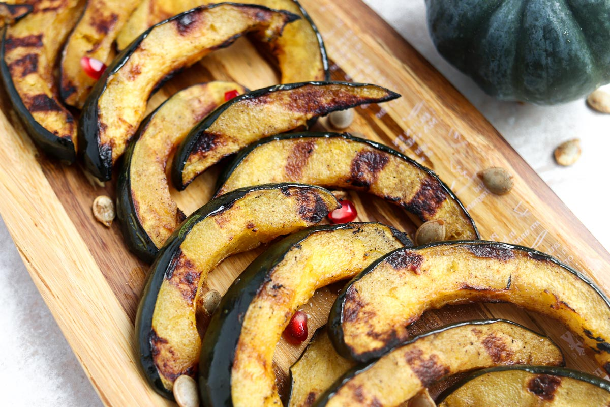 acorn squash slices with grill marks laying on a platter topped with roasted acorn seeds
