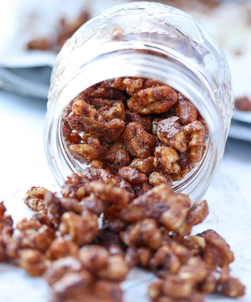 glass jar of walnuts roasted in spices spilling out of the jar