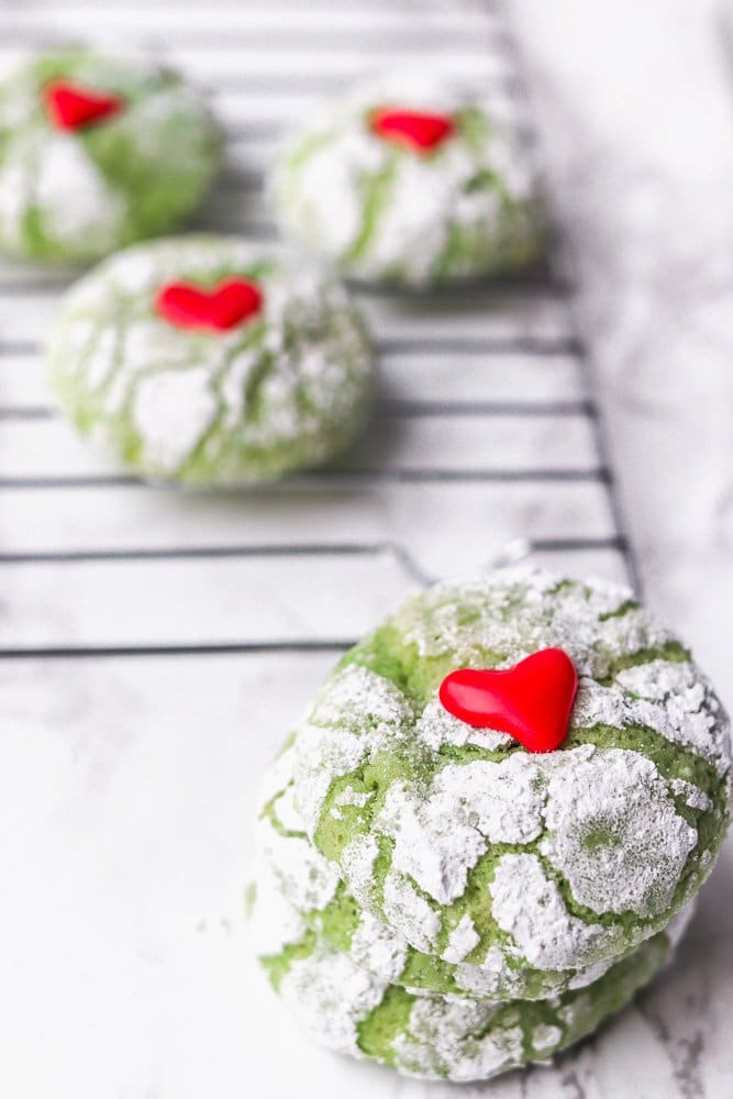 Green crinkle cookies stacked on top of each other with hearts on top.