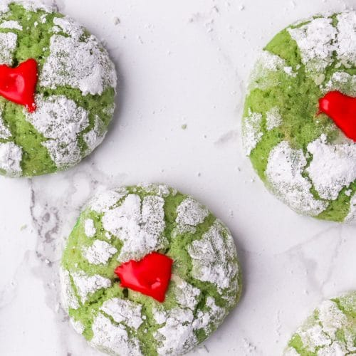 overhead shot of green cookies covered in powdered sugar and red hearts