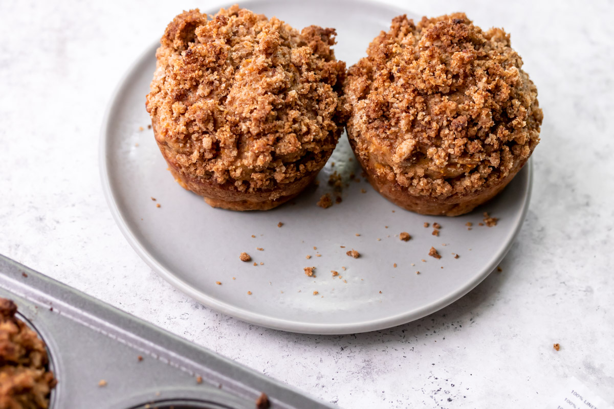 two banana carrot muffins with crumble on a plate