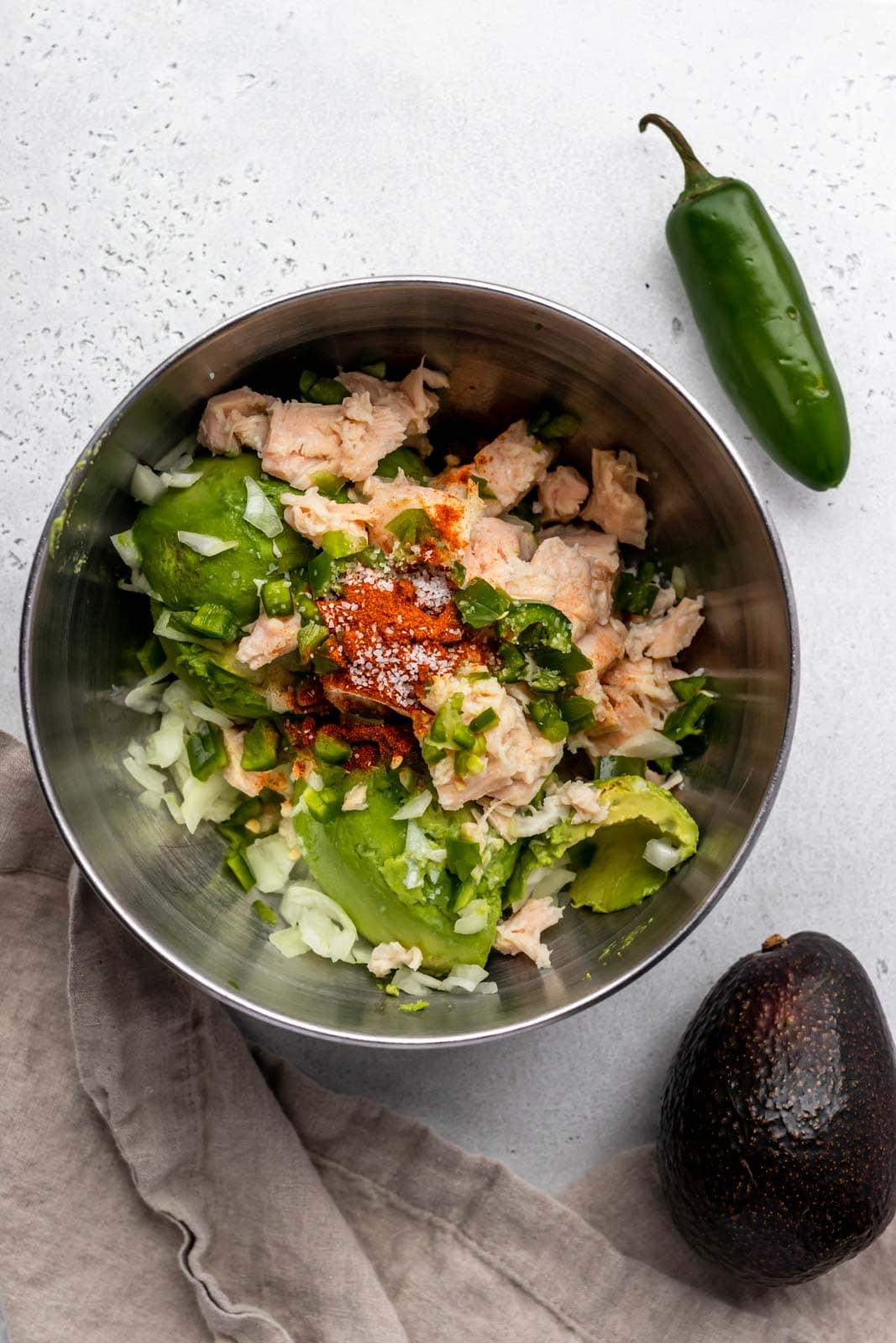 mixing bowl of canned chicken, avocado, jalapeno and spices