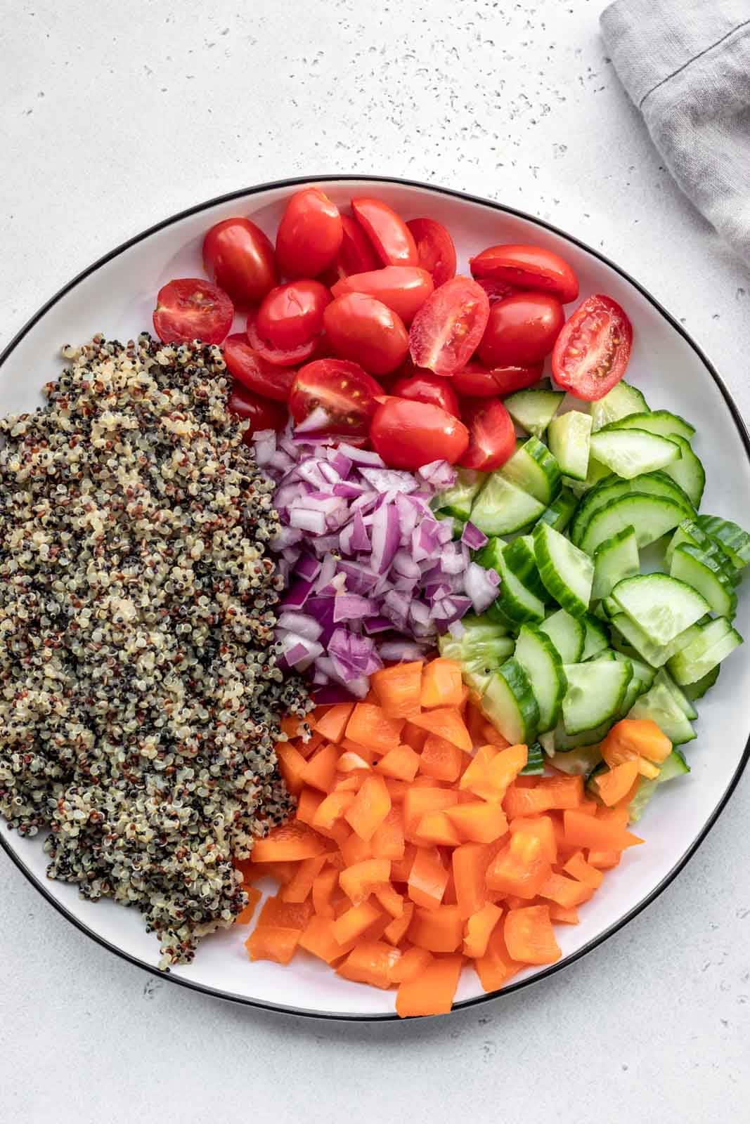 Platter of cooked quinoa, peppers, tomatoes and cucumber