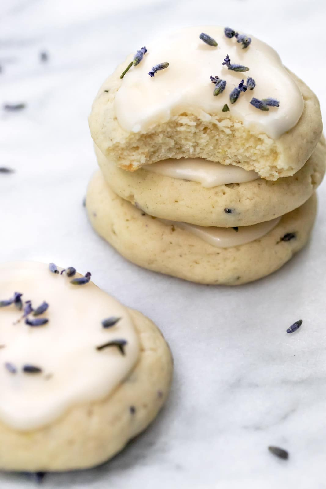 three stacked glazed cookies with lavender buds