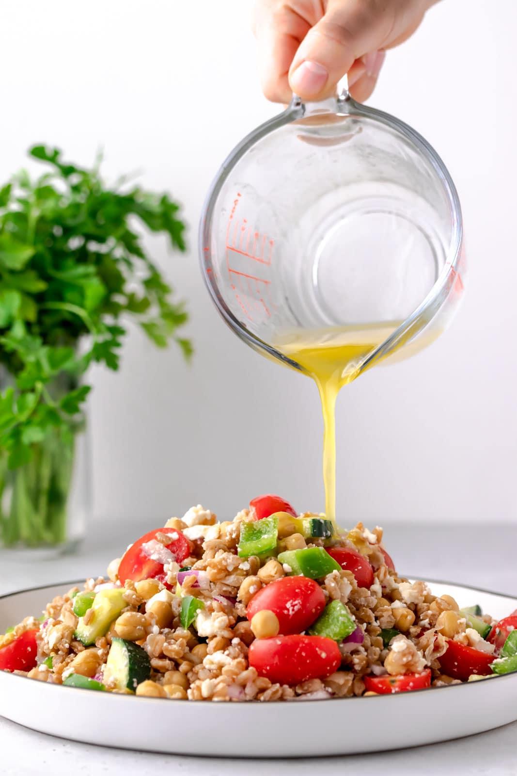 pouring citrus vinaigrette over salad