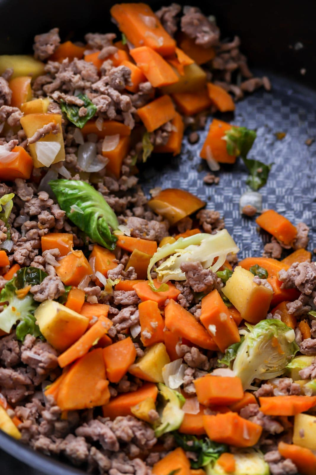 brussel sprous apples sweet potatoes and turkey in a pan