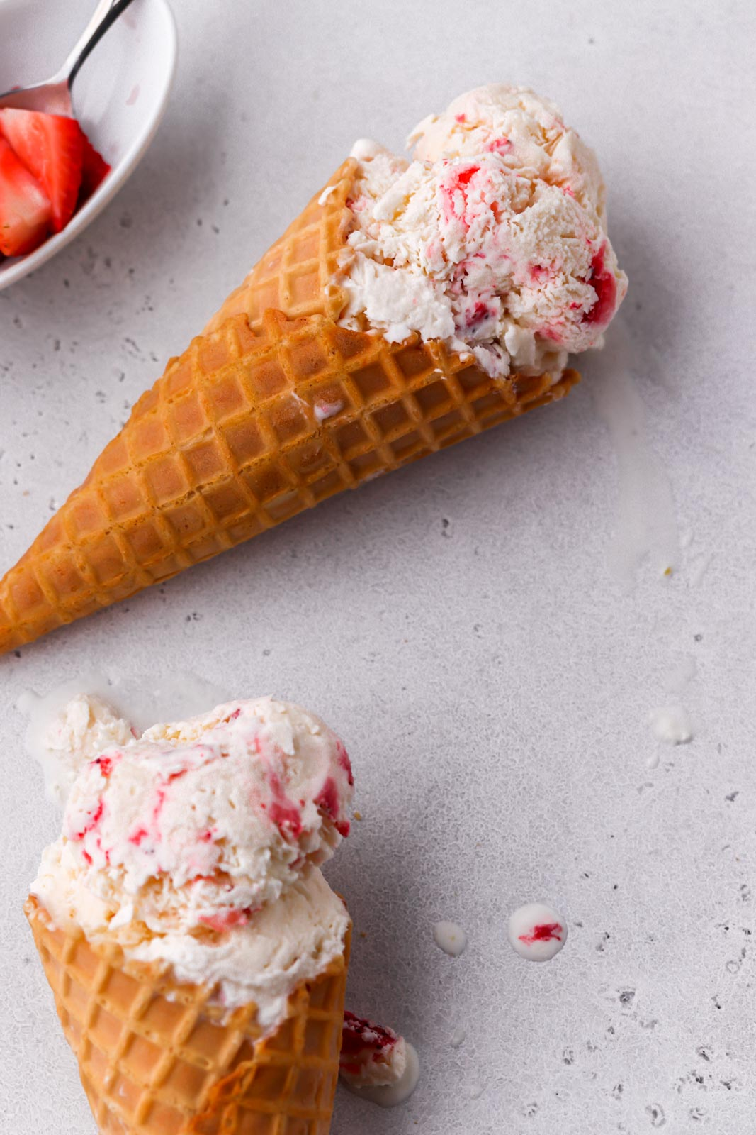 two ice cream cones with strawberries