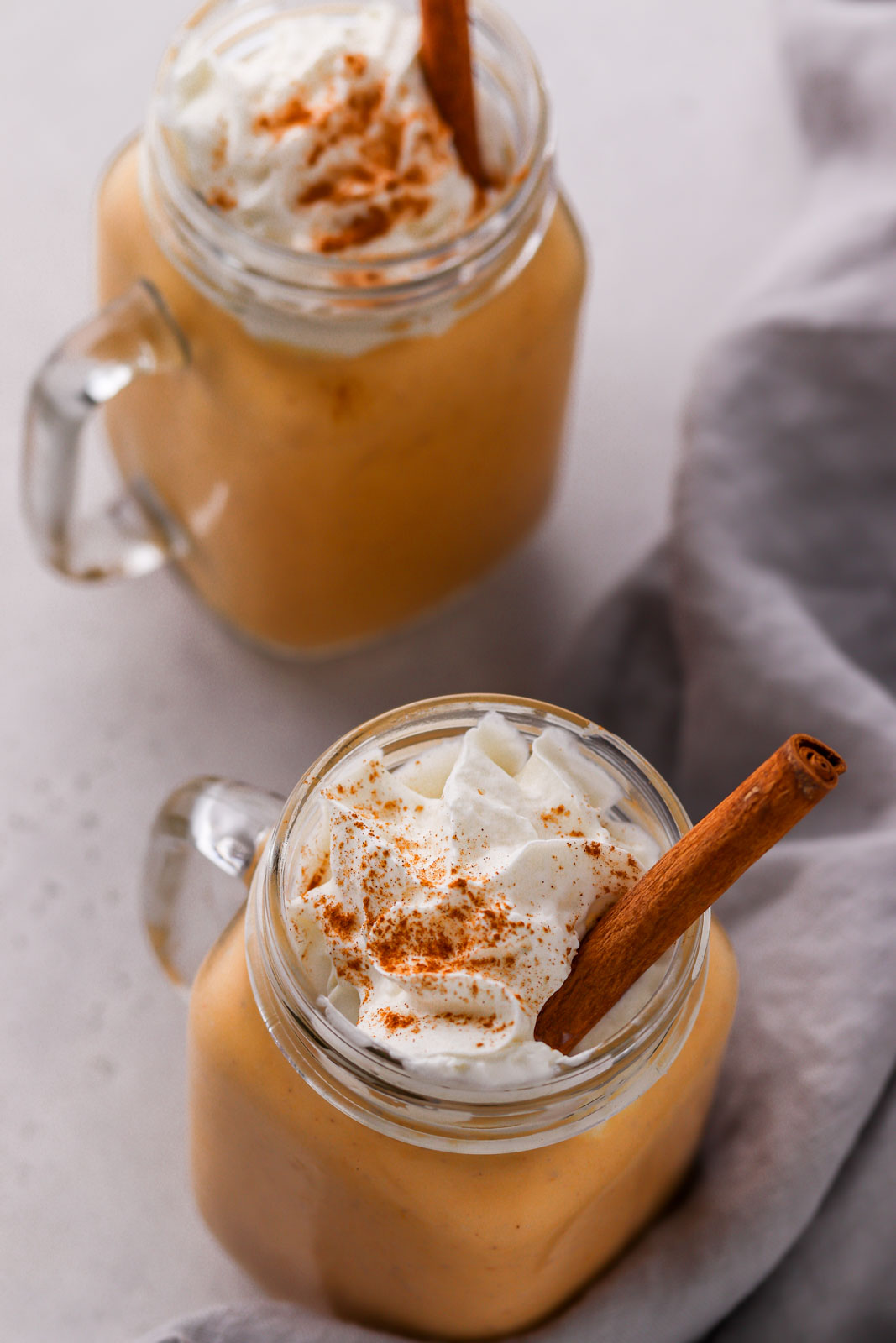 two fall spiced smoothies with cinnamon sticks
